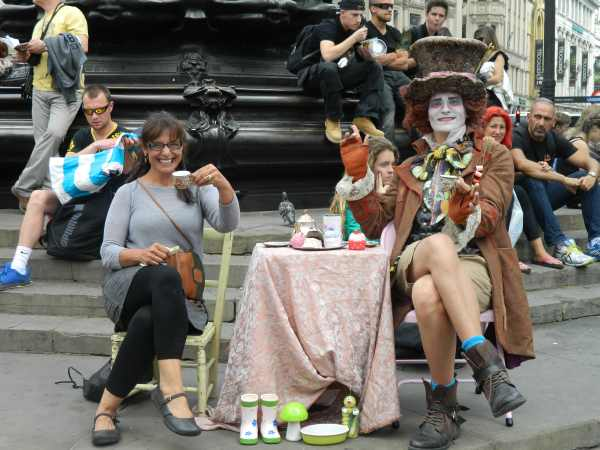 Enjoying tea with a street performer in Piccadilly Circus.