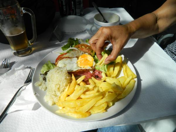 Typical Portuguese meal.  Fries on one side, rice on the other and a little piece of  meat in the middle.  A basket of bread is on the side.  Starch!